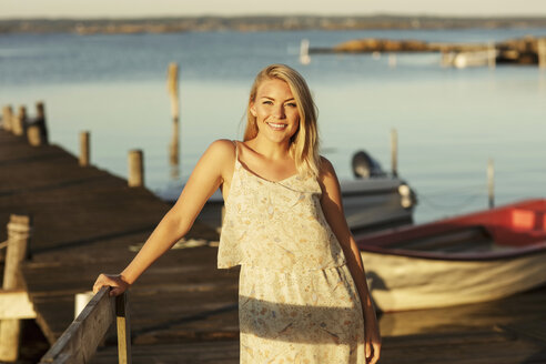 Portrait of smiling blond woman standing by railing at jetty - MASF01404