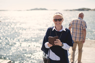 Portrait of smiling senior woman wearing sunglasses while holding mobile phone against lake - MASF01416