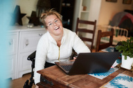 Portrait of smiling disabled woman using laptop at table in house - MASF01419
