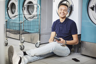 Portrait of smiling man holding calculator and studying while sitting besides washing machine - MASF01422