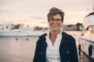 Portrait of smiling senior woman at harbor during sunset - MASF01434