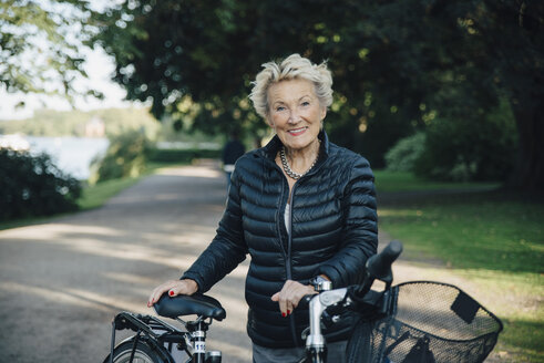 Portrait of smiling senior woman with bicycle in park - MASF01440