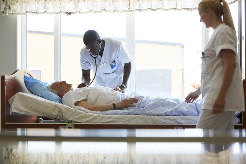 Nurse looking at male colleague examining senior man in hospital ward - MASF01476