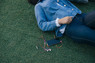 Midsection of teenage girl lying by mobile phone on grass - MASF01485
