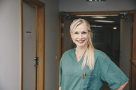 Portrait of confident female nurse standing in hospital corridor - MASF01488