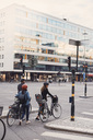 People walking with bicycles on street against building in city - MASF01494