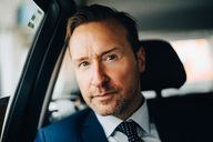 Portrait of confident mature businessman sitting taxi in city - MASF01512