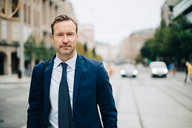 Portrait of confident mature businessman walking on street in city - MASF01515