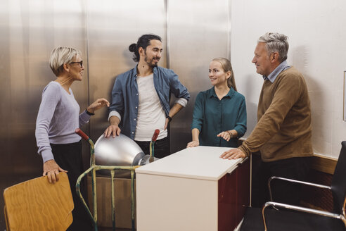 Multi-ethnic male and female business people with office equipment talking in elevator - MASF01524