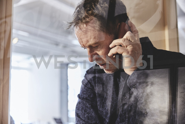 Mature male professional talking on smart phone seen from glass at office - MASF01539