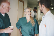 Medical colleagues discussing while standing in corridor at hospital - MASF01551