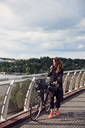 Mature woman talking through headphones while walking with bicycle on footbridge against sky - MASF01575