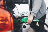 Midsection of man refueling car at gas station - MASF01578