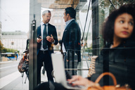 Mature male business coworkers talking while standing at bus stop seen from glass - MASF01593