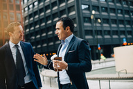 Mature male business colleagues talking while standing against buildings in city - MASF01602
