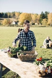 Mid adult man selling organic vegetables on table at farmer's market - MASF01620
