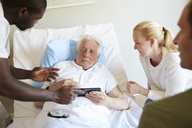 Male nurse showing digital tablet to senior man and couple at hospital ward - MASF01647