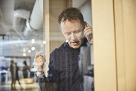 Mature businessman talking on mobile phone seen from glass at office - MASF01650