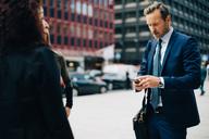Mature businessman using mobile phone while standing by female colleagues in city - MASF01698
