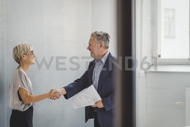 Mature businessman and businesswoman shaking hands in new office - MASF01707