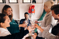 High angle view of happy young friends toasting wineglasses during lunch party - MASF01741
