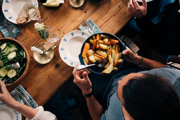 High angle view of man holding utensil of potatoes and carrots while sitting with friends - MASF01744