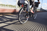 Low section of mature woman cycling on road - MASF01750