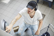 High angle view of young university student listening music while doing laundry - MASF01759