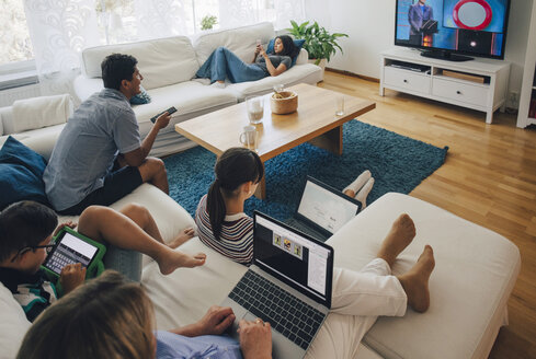 High angle view of family using technologies while relaxing in living room at home - MASF01765