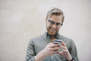 Happy male computer programmer using smart phone against beige wall in office - MASF01780