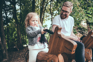 Happy father looking at daughter riding wooden horse in park - MASF01789