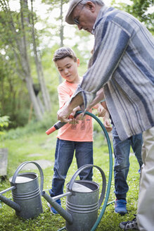Grandfather holding garden hose with grandsons by watering cans in back yard - MASF01792