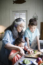 Grandmother assisting boy cutting cucumber on board in kitchen at home - MASF01795