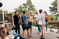 Happy friends greeting each other on cottage deck - MASF01816