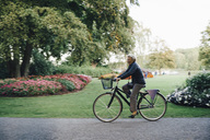 Full length side view of smiling senior woman riding bicycle in park - MASF01834