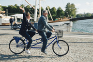 Full length side view of senior couple riding tandem bike on road in city during vacation - MASF01837
