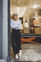 Full length portrait of smiling mature businesswoman standing arms crossed in new office - MASF01846
