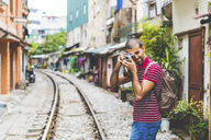 Vietnam, Hanoi, man in the city taking a picture with an old-fashioned camera - WPEF00211
