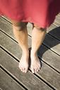 Feet of woman standing on deck - JOSF02165