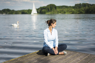 Relaxed woman sitting on jetty at a lake - JOSF02168