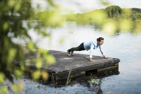 Woman doing pushups on jetty at a lake - JOSF02171