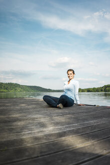 Smiling woman sitting on jetty at a lake - JOSF02174