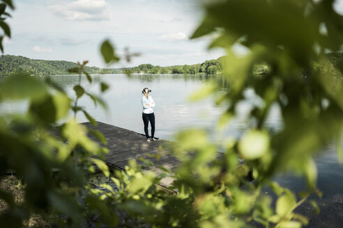 Woman standing on jetty at a lake wearing VR glasses - JOSF02177