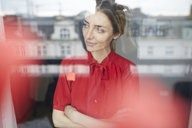 Portrait of smiling woman behind windowpane wearing red blouse - PNEF00588