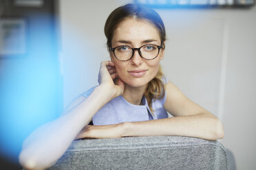 Portrait of smiling woman wearing glasses sitting on armchair - PNEF00591