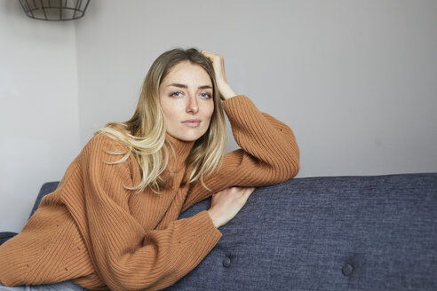 Portrait of blond woman relaxing on the couch - PNEF00597