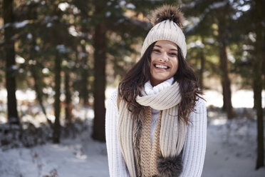 Portrait of laughing young woman wearing knitwear in winter forest - ABIF00279
