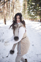 Portrait of laughing young woman having snowball fight in forest - ABIF00282