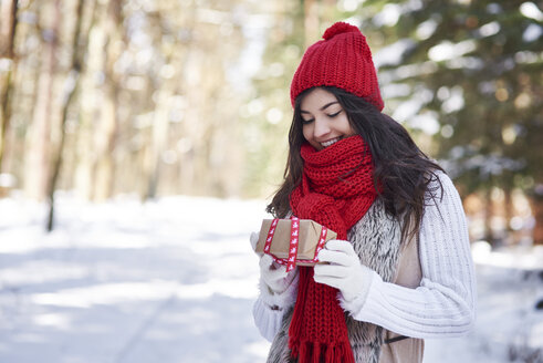 Portrait of happy young woman with Christmas gift in winter forest - ABIF00285