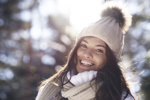 Portrait of happy young woman in winter forest - ABIF00288